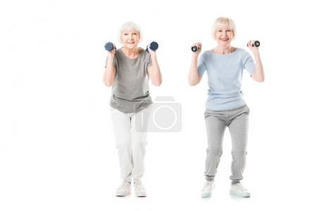 Sportives seniors souriantes, faire des exercices avec des haltères isolés sur blanc