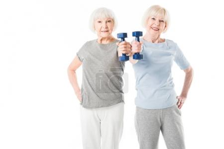 Photo for Two senior sportswomen doing exercise with dumbbell isolated on white - Royalty Free Image