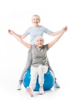 Photo pour Sportives seniors souriantes avec ballon de fitness isolé sur blanc - image libre de droit