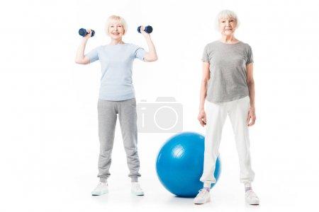 Photo pour Sportives seniors souriantes avec boule de remise en forme et haltères isolés sur blanc - image libre de droit