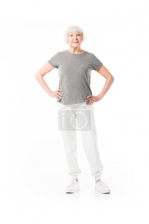 Senior sportswoman standing with hands on waist isolated on white