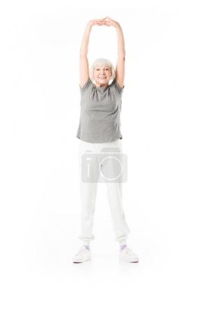 Photo for Smiling senior sportswoman with arms up doing excercise isolated on white - Royalty Free Image