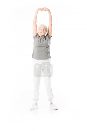 Smiling senior sportswoman with arms up doing excercise isolated on white