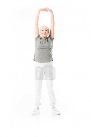 Photo pour Souriante sportive senior avec les bras vers le haut de faire de l'exercice isolé sur blanc - image libre de droit