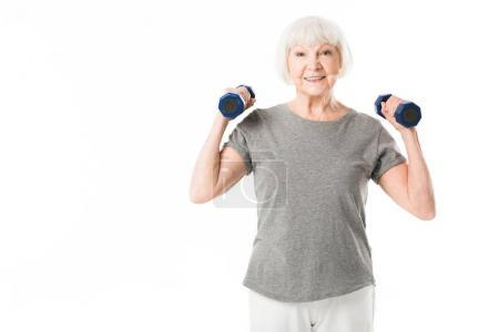 Photo for Smiling senior sportswoman doing excercise with dumbbells isolated on white - Royalty Free Image