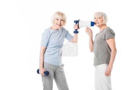 Two senior sportswomen with dumbbells and megaphone isolated on white