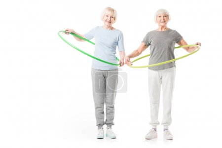 Two senior sportswomen doing hula hoop excercise isolated on white