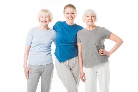 Portrait de trois sportives souriantes isolé sur blanc