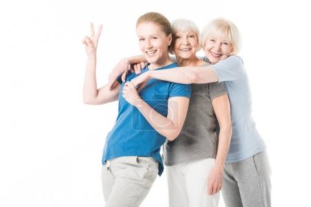 Mature sportswoman showing peace gesture while two senior sportswomen embracing her isolated on white
