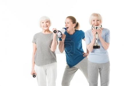 Coach with megaphone and sportswomen with dumbbells and trophy isolated on white