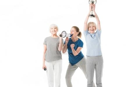 Coach and smiling sportswomen with dumbbells and trophy isolated on white