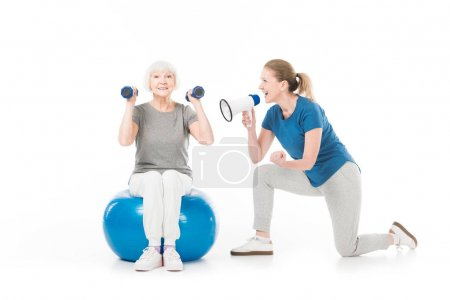 Coach with megaphone and sportswoman with dumbbells and fitness ball isolated on white