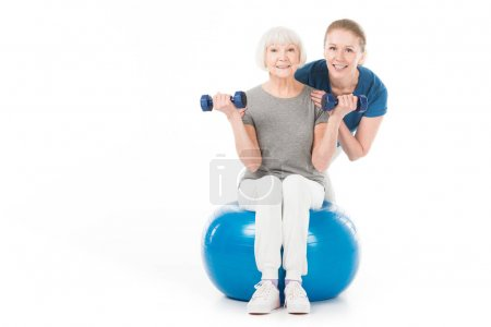 Portrait of coach and sportswoman with dumbbells and fitness ball isolated on white