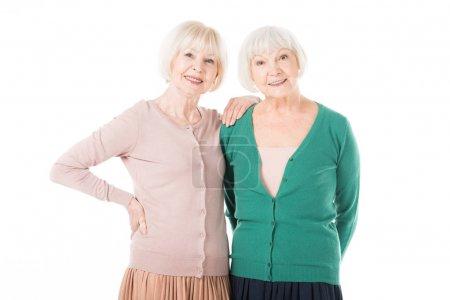 Two stylish senior women standing isolated on white