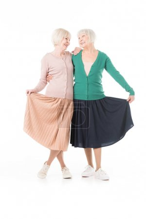 Smiling stylish senior women holding skirts isolated on white