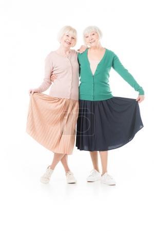 Portrait of smiling stylish senior women holding skirts isolated on white