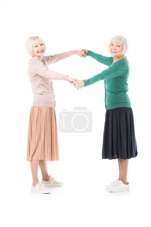 Two stylish senior women holding hands of each other isolated on white