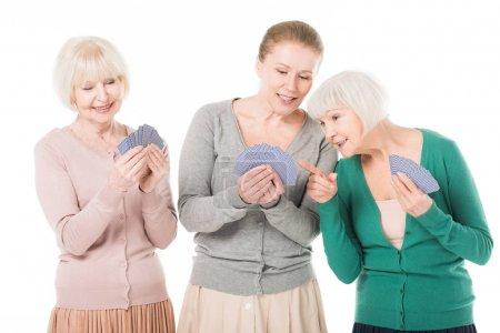 Three stylish smiling women playing cards isolated on white