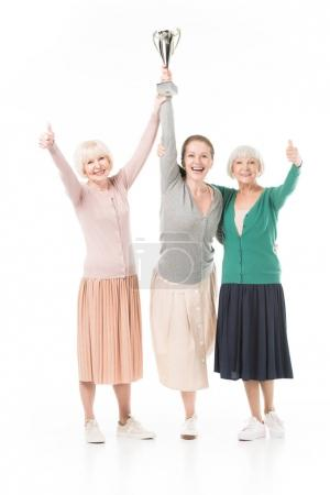 Three smiling stylish women celebrating with trophy cup isolated on white
