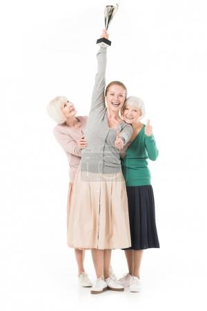 Happy stylish women showing thumb up gesture and celebrating with trophy isolated on white