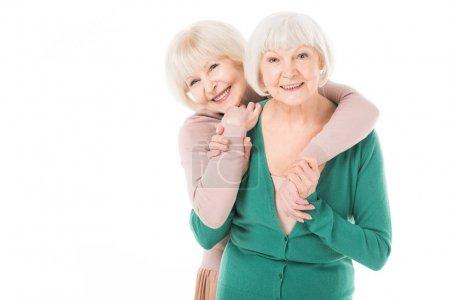 Two senior stylish women hugging isolated on white