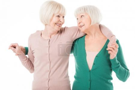 Two senior stylish women embracing isolated on white