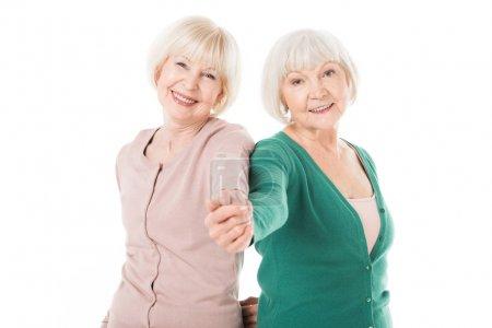 Smiling stylish senior women holding hands isolated on white