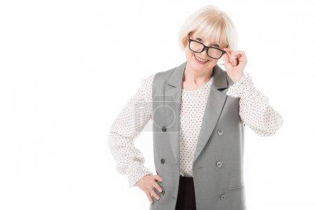 Smiling stylish senior businesswoman looking over eyeglasses isolated on white