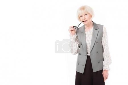 Stylish senior businesswoman holding eyeglasses near lips isolated on white