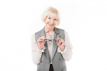 Photo for Smiling stylish senior businesswoman holding eyeglasses isolated on white - Royalty Free Image