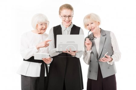 Three stylish businesswomen with laptop, digital tablet, smartphone and eyeglasses isolated on white