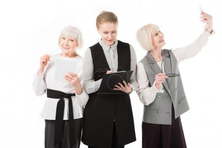 Three stylish businesswomen with digital tablet, clipboard and smartphone isolated on white