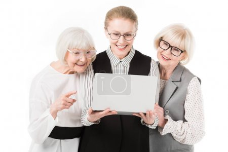 Three stylish businesswomen in eyeglasses looking at laptop isolated on white