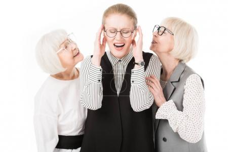 Mature stylish businesswoman shutting ears between two senior businesswomen in eyeglasses isolated on white