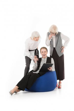 Photo for Three stylish senior businesswomen with clipboard and armchair isolated on white - Royalty Free Image