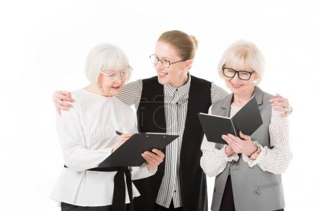 Two senior stylish businesswomen writing in clipboard and textbook while mature businesswoman holding their shoulders isolated on white