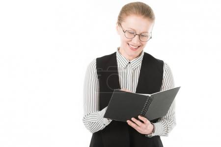 Smiling stylish mature businesswoman in eyeglasses holding textbook isolated on white