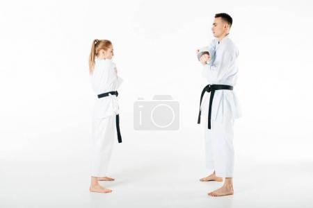 side view of karate fighters stretching hands isolated on white