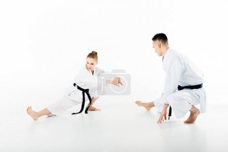 karate fighters stretching legs isolated on white