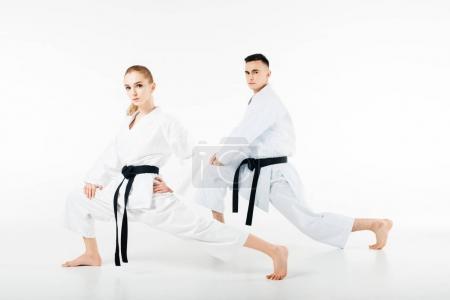 Photo pour Combattants de karaté étirant les jambes et regardant la caméra isolée sur blanc - image libre de droit