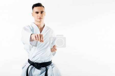 male karate fighter performing hit and looking at camera isolated on white