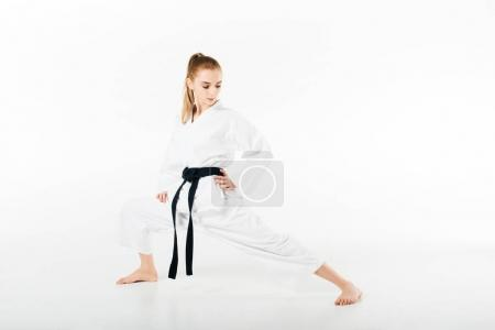 female karate fighter stretching legs isolated on white
