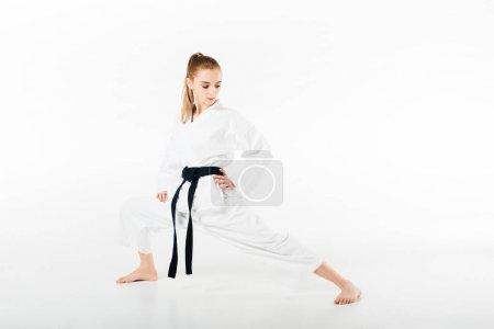 Photo pour Combattant de karaté femelle étirant les jambes isolées sur blanc - image libre de droit
