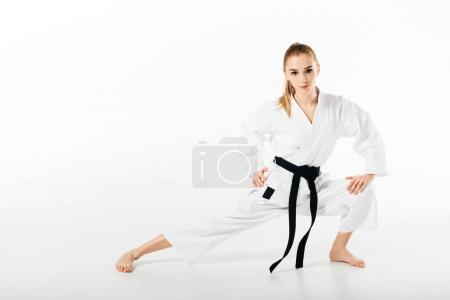 female karate fighter stretching and looking at camera isolated on white
