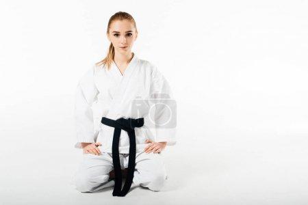 Photo pour Combattant de karaté féminin assis et regardant la caméra isolée sur blanc - image libre de droit