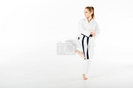 female karate fighter standing on one leg isolated on white