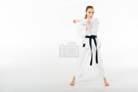 Photo for Female karate fighter stretching hands and looking at camera isolated on white - Royalty Free Image