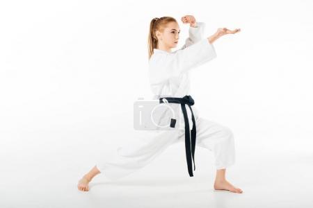 Photo pour Fille en kimono entraînement karaté isolé sur blanc - image libre de droit