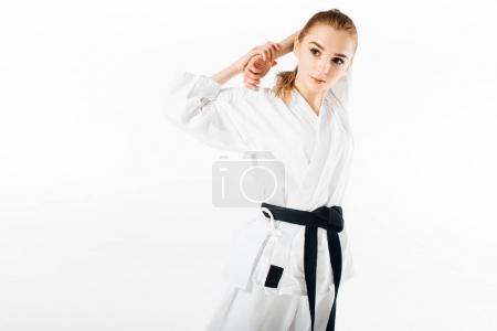 Photo pour Combattant de karaté femelle étirant les épaules isolées sur blanc - image libre de droit