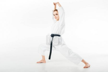 female karate fighter stretching isolated on white